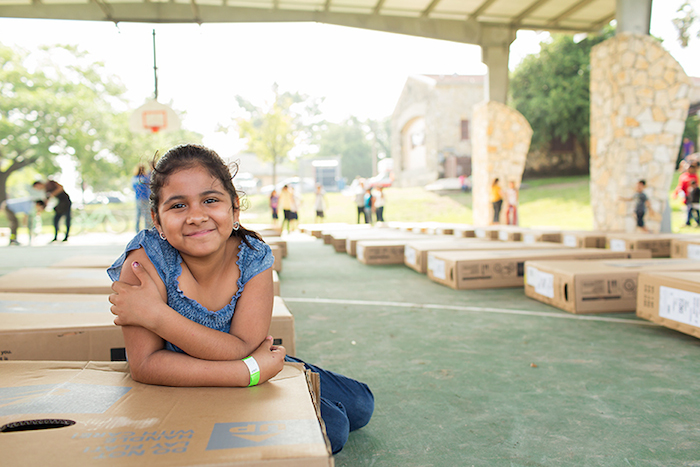Ellie, 11, poses for a photo before assembling her new bike during the Chiquitas Ciclistas event in the Eastside. Photo by Rachel Chaney