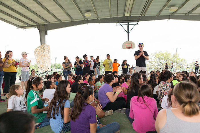 Cristian Sandoval, founder of Earn-A-Bike Co-op, recognizes the girls' hard work and the hard work of volunteers during the Chiquitas Ciclistas event in the Eastside. Photo by Rachel Chaney