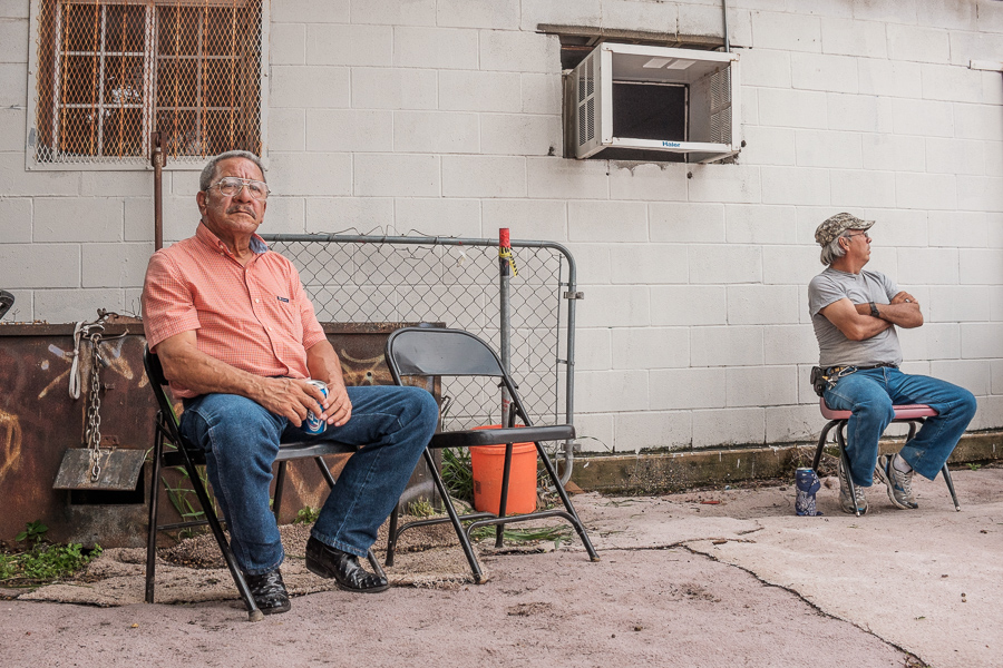 Two spectators watch a wrestling match. Photo by Scott Ball.