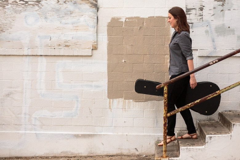 Nicolette Good walks down a staircase with her guitar. Photo by Scott Ball.