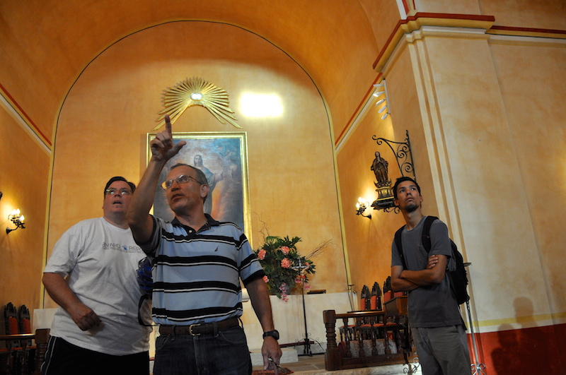 Fr. David Garcia points to the small openings in Mission Concepción that allow two beams of light to illuminate the Virgin Mary's face and altar floor at 6:30 p.m. every Aug. 15 for the Assumption of the Virgin Mary into Heaven. Photo by Iris Dimmick.