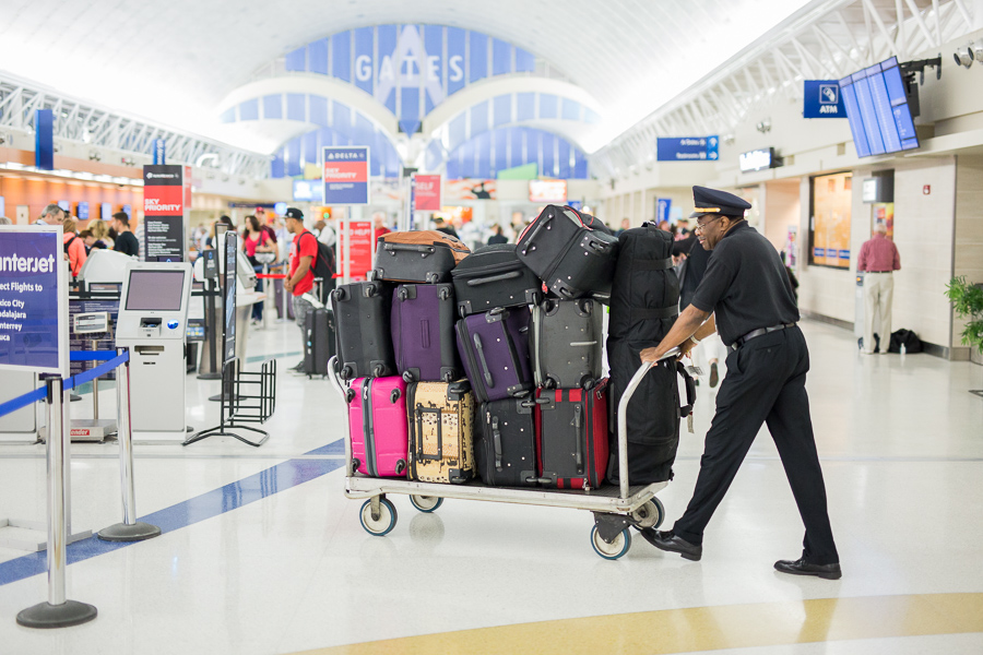 A baggage handler transports luggage in terminal A. Photo by Scott Ball.