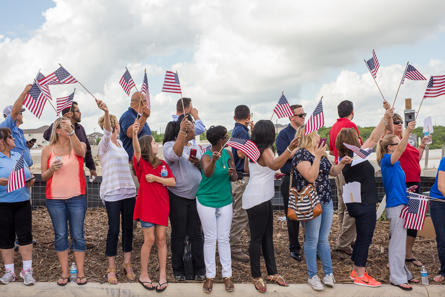 Attendees wave flags as the families arrive. Photo by Scott Ball.