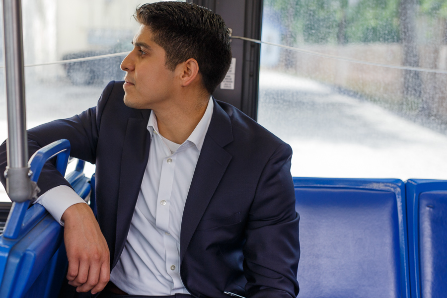 Councilman Rey Saldaña looks down the row of seats on a VIA bus. Photo by Scott Ball.