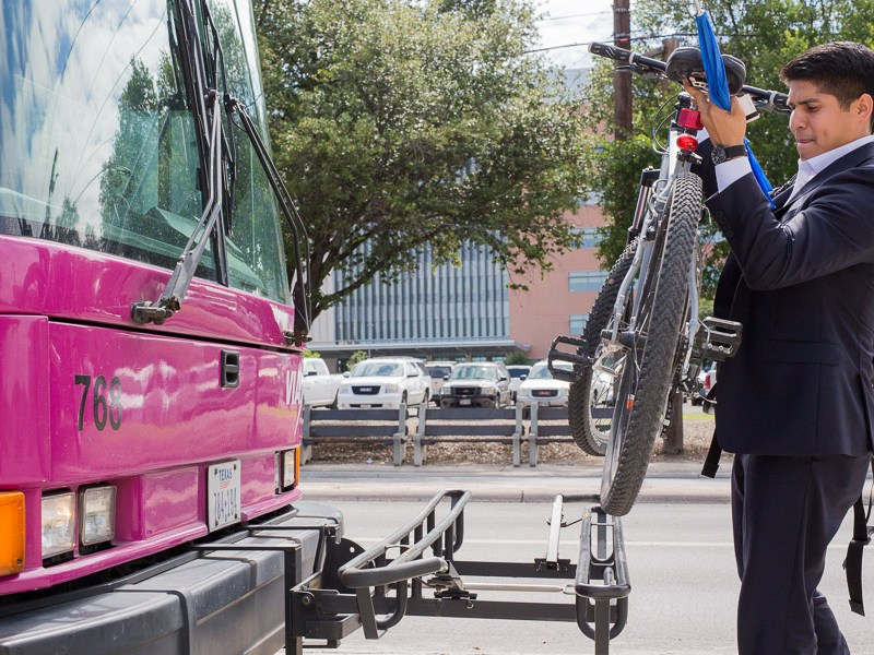 Councilman Rey Saldaña removes his bicycle from the front rack of a VIA bus. Photo by Scott Ball.