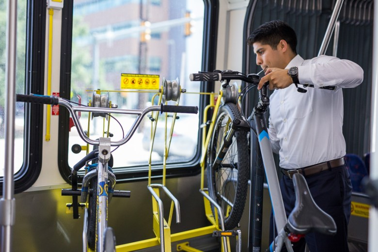Councilman Rey Saldaña puts his bicycle in an on-board bike rack only available on VIA Primo. Photo by Scott Ball.