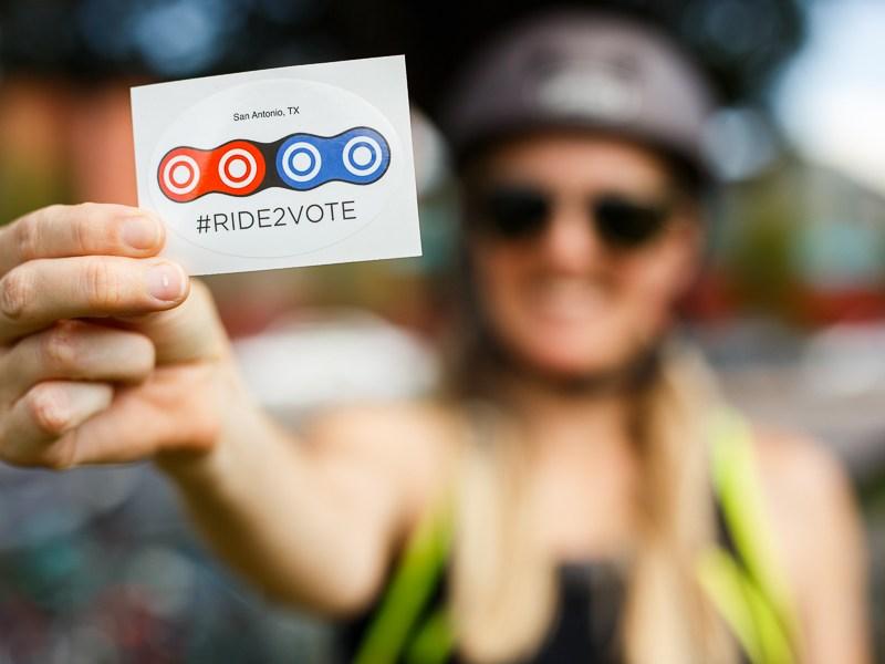 Rachel McDevitt holds up a #RIDE2VOTE sticker. Photo by Scott Ball.