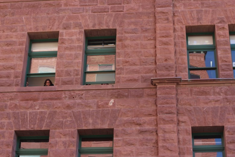A woman watches the rededication ceremony from a Bexar County Courthouse window. Photo by Joan Vinson.