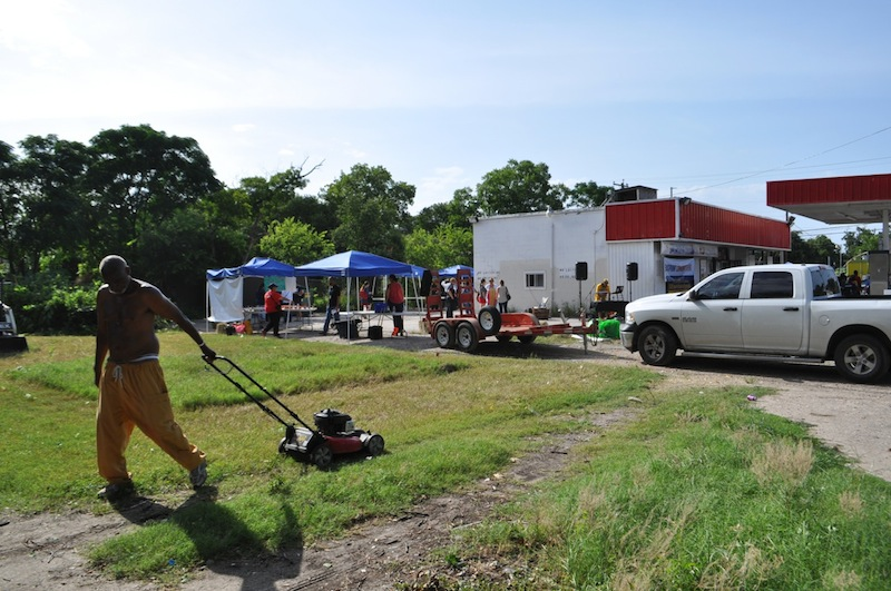 Volunteers clear and mow the vacant lot next to the Handy Shop. Photo by Iris Dimmick.