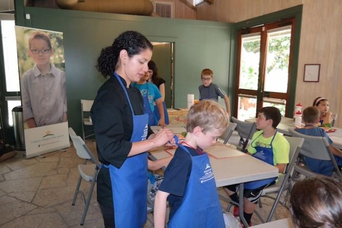 Chef Maria Palma ties an apron on a boy. Courtesy photo.