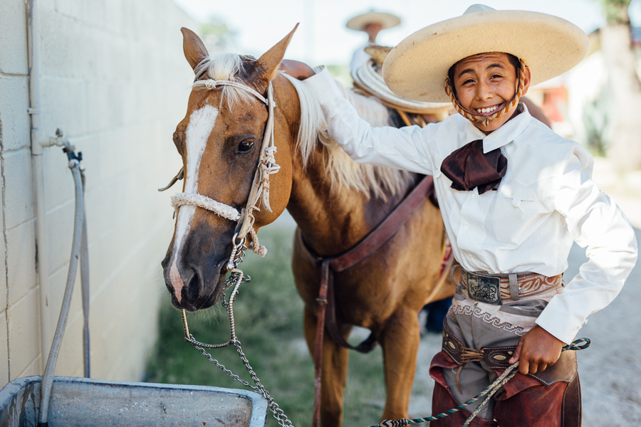 Charro Raymond poses for a photo with his horse while it gets a drink. Photo by Scott Ball.