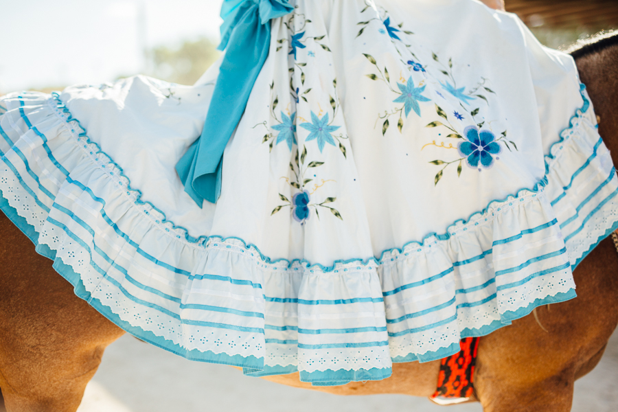 Escaramuzas ride wearing beautiful dresses that drape over the body of the horse. Photo by Scott Ball.