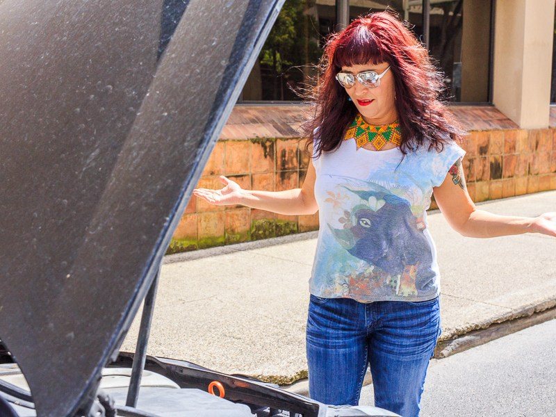 """Marisela lifts open her hood asking herself """"what's the deal?"""". Photo by Scott Ball."""