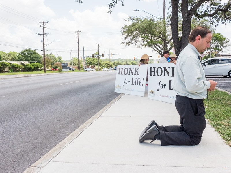 Danny Petri kneels on the sidewalk and prays in front of Planned Parenthood. Photo by Scott Ball.