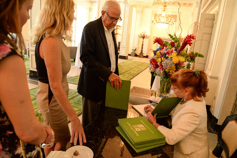 """Gaylon Finklea Hecker signs copies of her book, """"Dusting Off a Legend: The St. Anthony Hotel,"""" at a reception at the hotel July 21, 2015. Photo by Annette Crawford."""