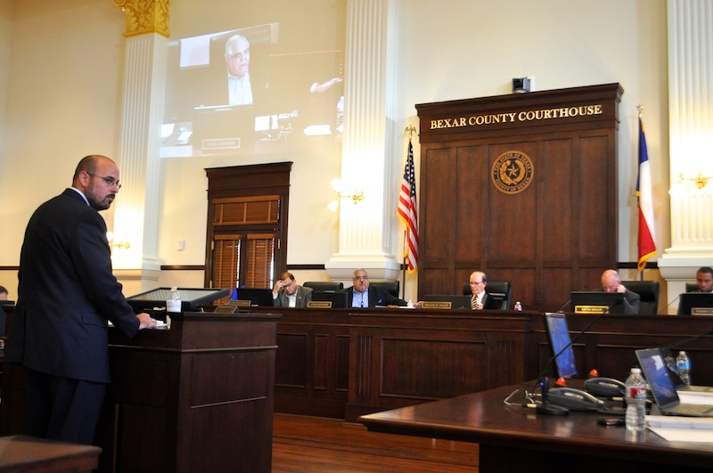 """Bexar County Department of Management and Finance Director Seth McCabe (foreground) presents budget adjustments to the Bexar County commissioners (from left) Sergio """"Chico"""" Rodriguez (Pct. 1), Paul Elizondo (Pct. 2), County Judge Nelson Wolff, Kevin Wolff ( Pct. 3) and Tommy Calvert (Pct. 4). Photo by Iris Dimmick."""