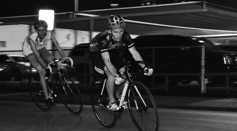 Racers round a corner while riding during an underground, nighttime bike criterium (a short, timed route – winner makes the most laps) in June 2013. Photo by David Rangel.