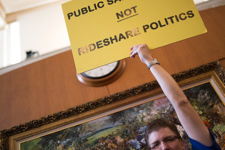 Mark Tidwell, a cab driver against ride sharing holds up a sign in the council chambers. Photo by Scott Ball.