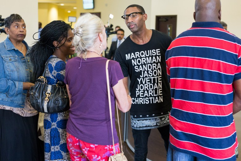 Local activist Mike Lowe greets friends as they arrive. Photo by Scott Ball.