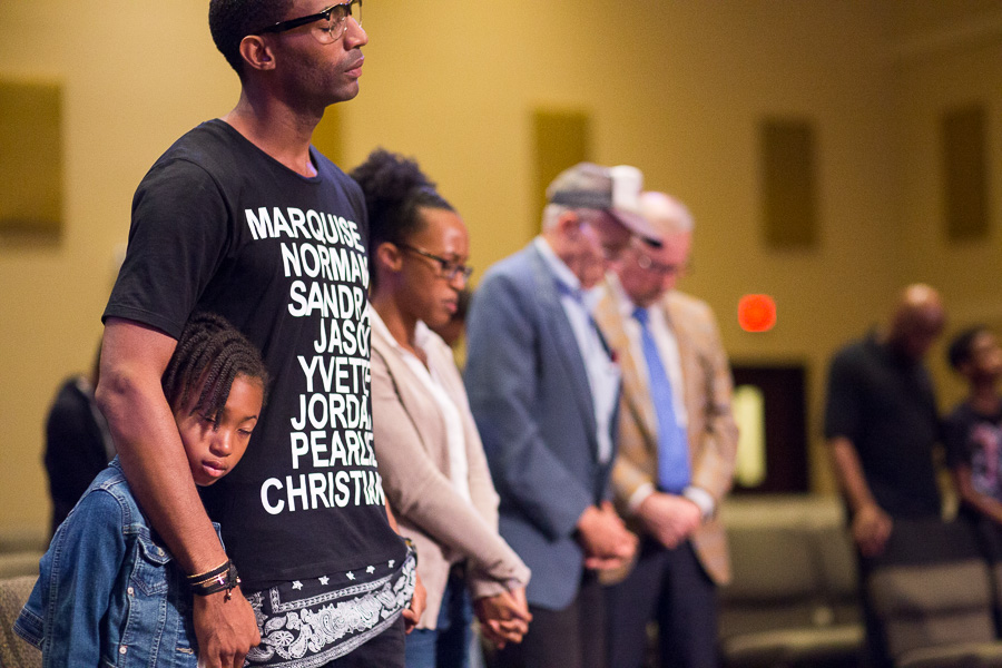 Local activist Mike Lowe stands during a moment of silence with his family. Photo by Scott Ball.