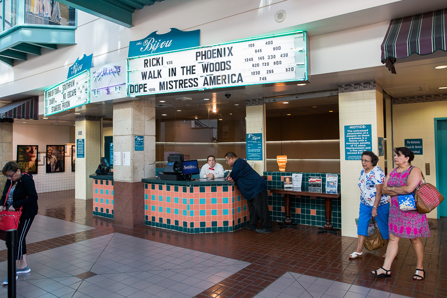 Moviegoers walk pass the ticket booth at The Bijou, owned and operated by Santikos Theatres. Photo by Scott Ball.