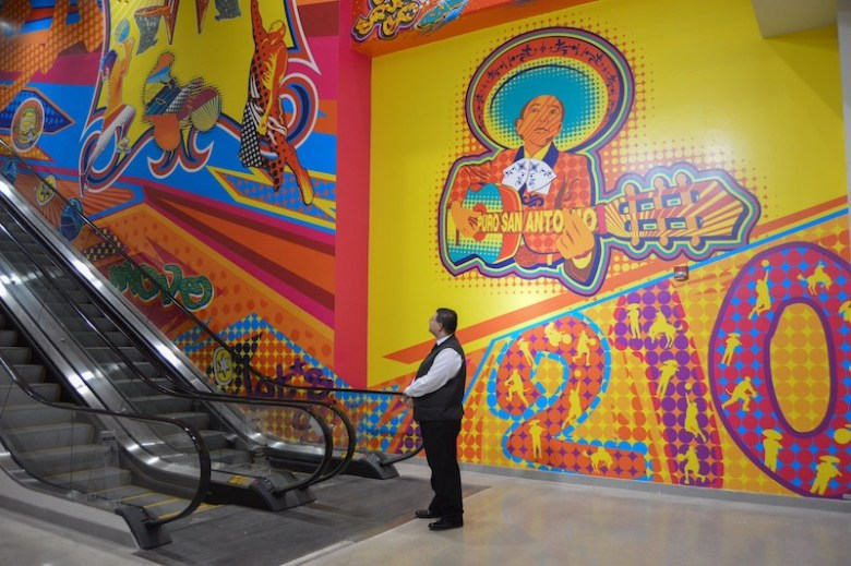 """Usher John Moreno waits by a new mural, """"Light It Up,"""" by artist Elizabeth Carrington, to direct Spurs fans in the right direction. Photo by Lea Thompson."""
