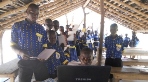 Children wait in line to use the internet to participate in a course through PenPal Schools. Courtesy photo.