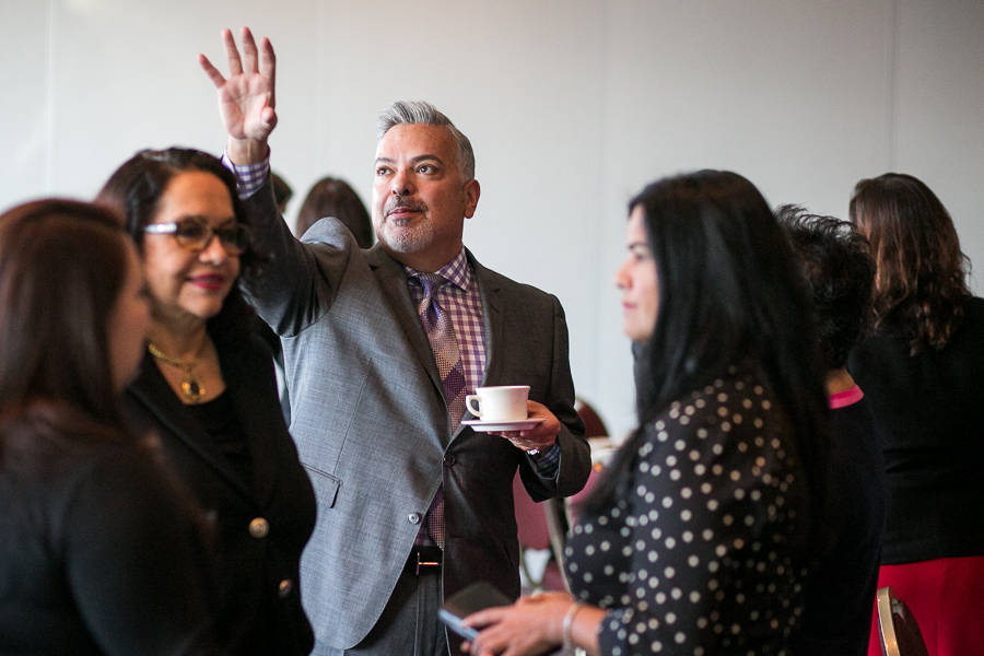 Henry Munoz III raises his hand as he speaks with guests. Photo by Scott Ball.