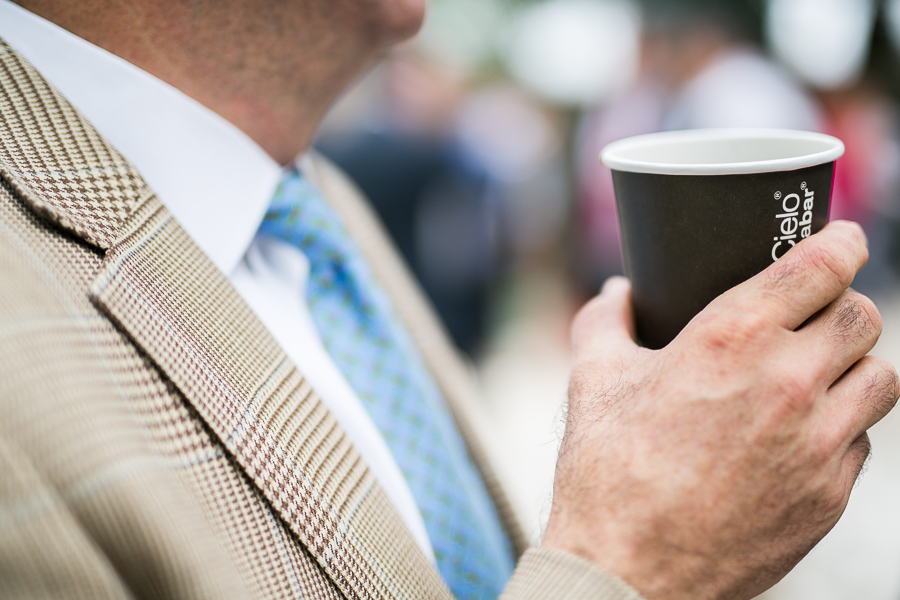 A guest holds up a cup of coffee from Cafe Punta del Cielo. Photo by Scott Ball.