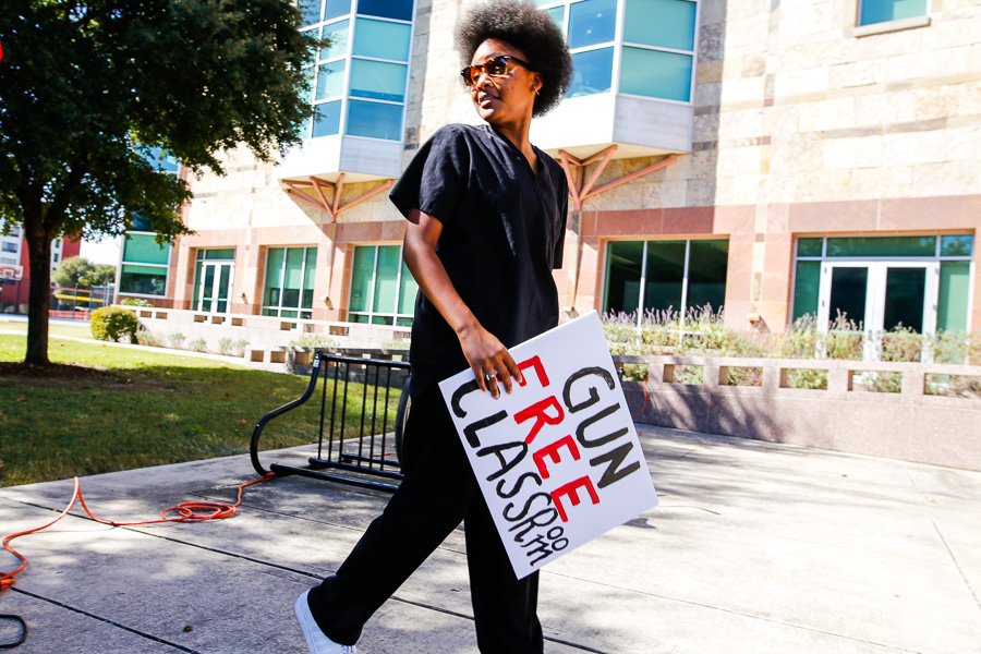 Graduate student Ayanna Allen walks with a sign in protest of guns on campus. Photo by Scott Ball.