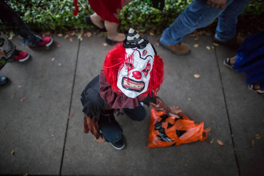 A trick-or-treater drops his bag of candy. Photo by Michael Cirlos.