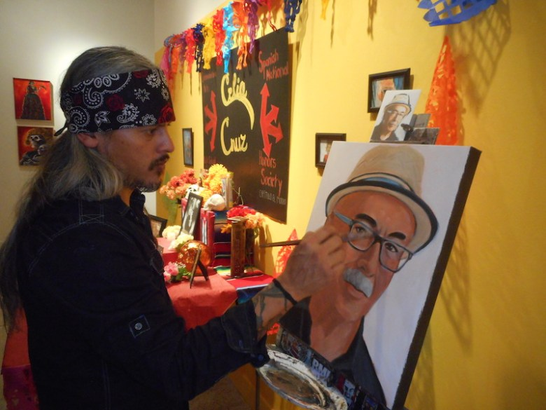 John Eric Delazerda paints a portrait of Juan Felipe Herrera at the Guadalupe Gallery Tuesday night. Photo by Don Mathis.
