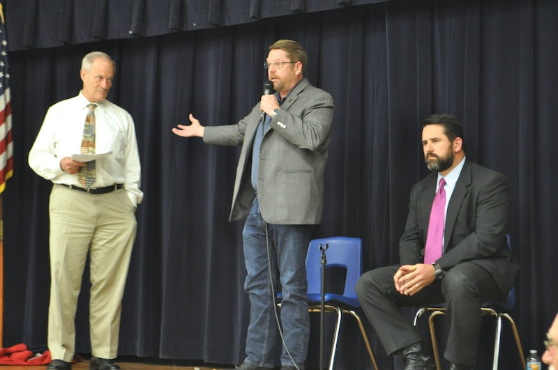 Tommy Adkisson, SAPOA President Mike Helle, and Deputy City Manager Erik Walsh on stage at Highland Hills Elementary. Photo by Iris Dimmick.