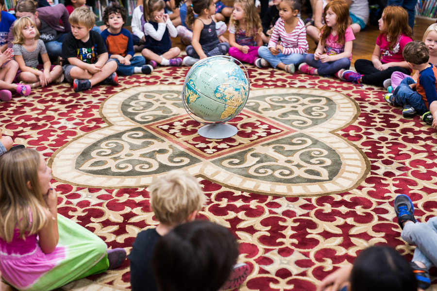 Students surround the globe at the end of circle time, just before they break for class. Photo by Scott Ball.