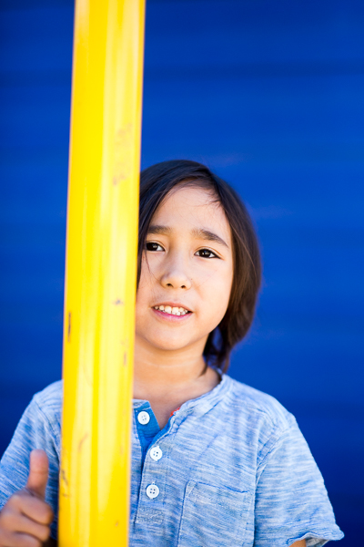 A Circle School student poses for a photo behind playground equipment. Photo by Scott Ball.