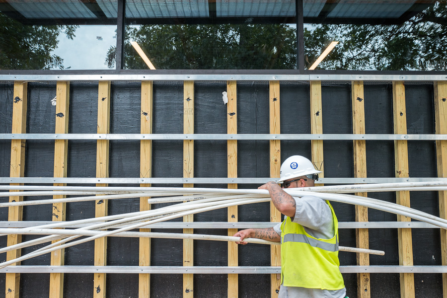 A construction worker walks by the future location of the living wall with irrigation lines. Photo by Scott Ball.