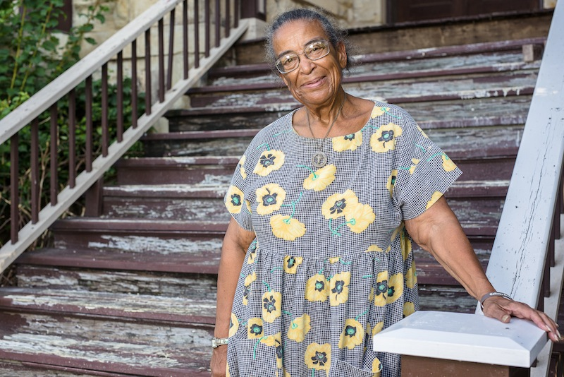 Nettie Hinton stands on her front porch in Dignowity Hill. Photo by Scott Ball.