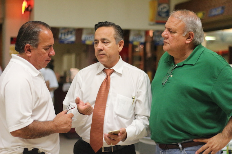 From left: Tomás Uresti, state Sen. Carlos Uresti, and Bexar County Tax-Assessor-Collector Albert Uresti discuss polling numbers. Photo by Joan Vinson.