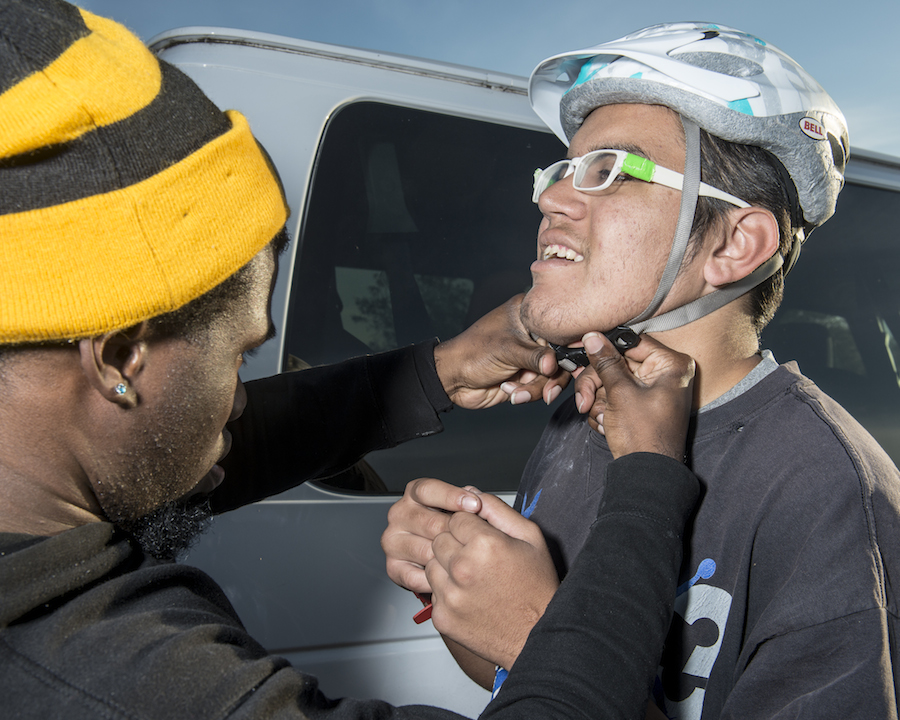 Victor Ross (left) helps Joshua Cooke to buckle his helmet. Photo by Matthew Busch.