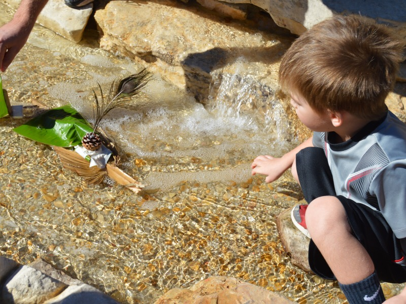 "Ryder Bufe, age 5, releases his boat into ""Will's Stream"" at the DoSeum. Photo by Lea Thompson."