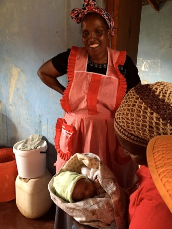 Thembile's 3-week-old baby is held by our translator, Thimbe. Photo by Casey Miller.