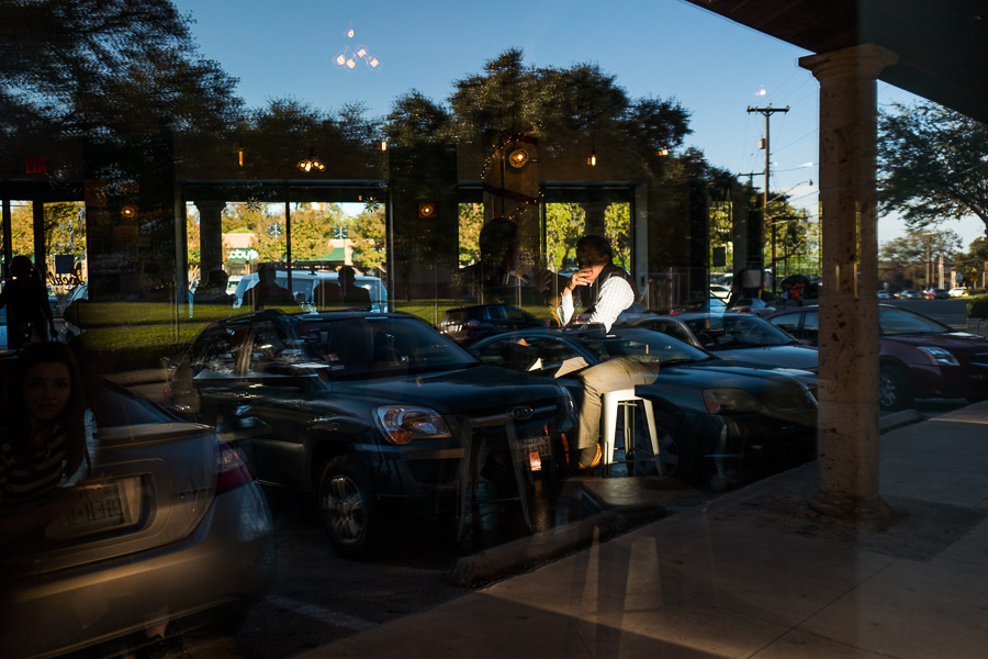 Customers relax inside Local Coffee as the reflection of the outside parking lot is filled with vehicles. Photo by Scott Ball.
