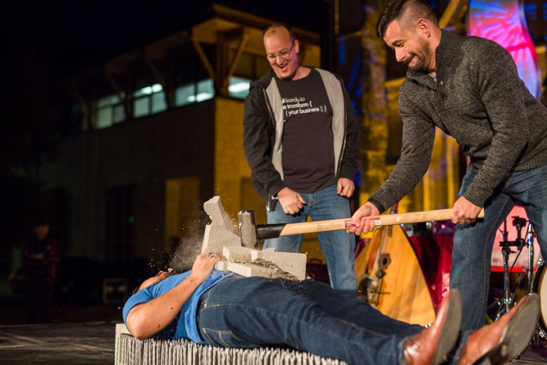 Geekdom staff member Christian Torres smashes a cinder block on local illusionist Jacob Espinoza as he lays on a bed of nails, Patrick Asher looks on. Photo by Scott Ball.