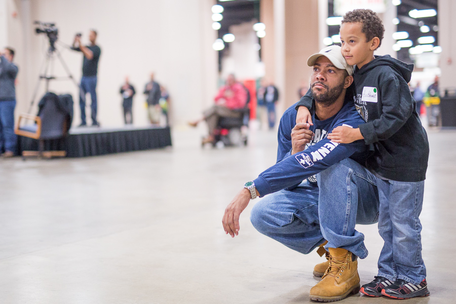 Father and son volunteers look on as a prayer is said. Photo by Scott Ball.