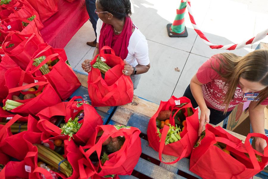 Pre-K 4 SA Co-Master Teacher Cashelle Johnson (left) and H-E-B Partner Whitney Schafman prepare bags full of produce for donation. Photo by Scott Ball.