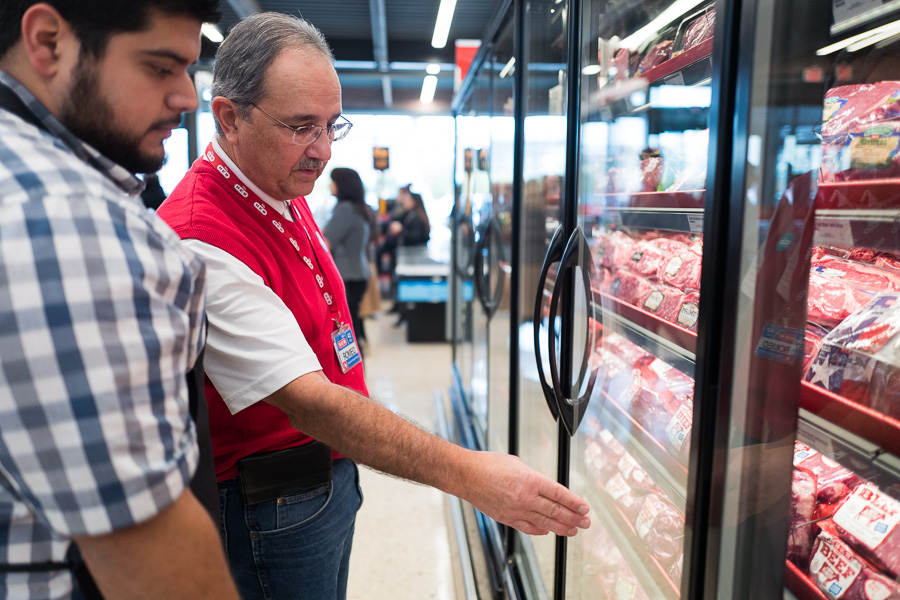 H-E-B Meat Market Lead and employee of 7 years Nolan Barrera (left) listens as 42 year veteran Romeo Garza as he discusses the selections of meat. Photo by Scott Ball.