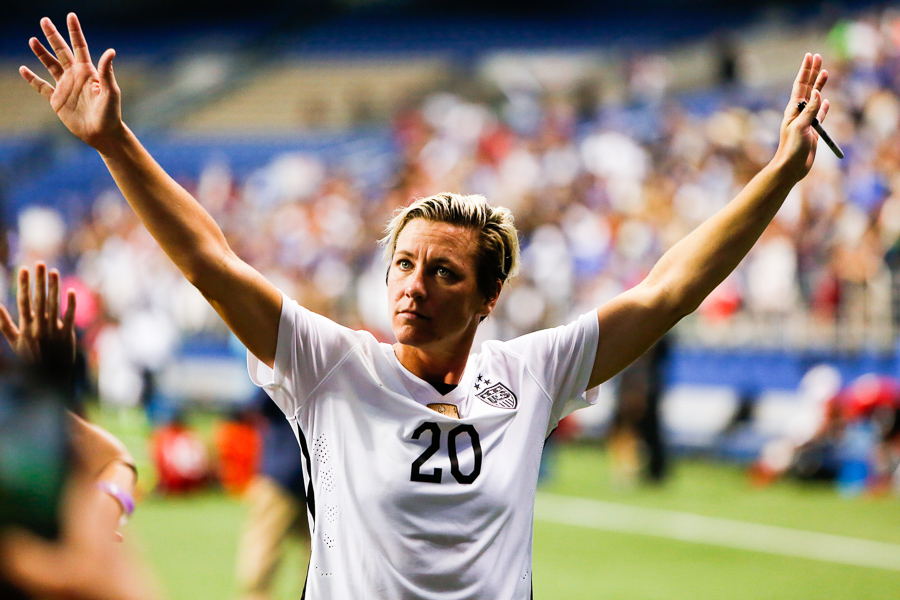 Abby Wambach raises her arms as she leaves the field. Photo by Scott Ball.