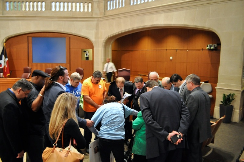 Attendees bow their heads in prayer after the City Council's vote. Photo by Iris Dimmick.
