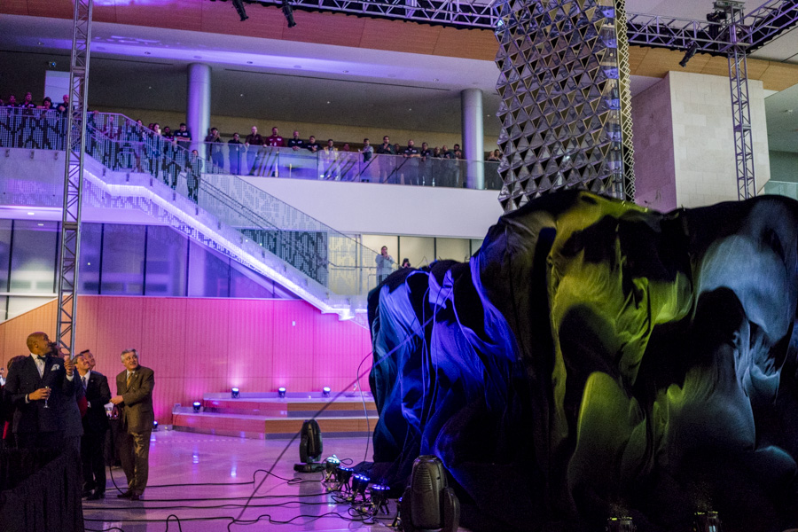"""A large curtain drops to reveal """"Liquid Crystal,"""" a public art installation by Jason Bruges in the center of the Henry B. Gonzalez's atrium lobby. Photo by Kathryn Boyd-Batstone."""