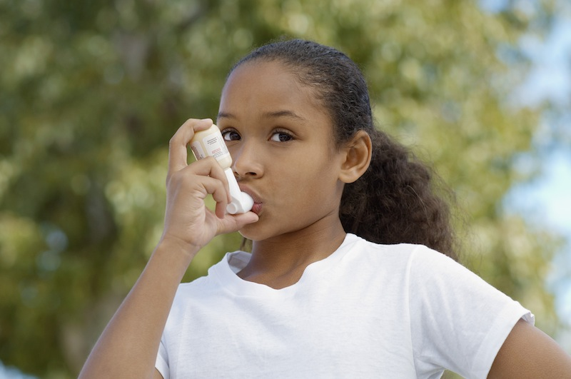 A young girl uses her inhaler. Photo courtesy of Moms Clean Air Force of Central TX.